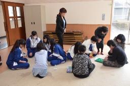 一緒にゲームをして遊ぶ高校生と子どもたち