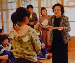 子どもたちに図書カードをプレゼントする井田会長