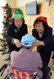 手作りの帽子を利用者に贈る内田会長(右)ら