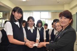 1年生の代表にカードを手渡す布川会長(右)
